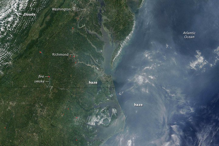 The Moderate Resolution Imaging Spectroradiometer (MODIS) on NASA's Terra satellite captured this photo-like image of haze in the Eastern United States on July 26, 2005. Easier to see over the ocean, gray-tan haze hangs over the Mid-Atlantic region. Fires are marked with red dots. The image illustrates that haze is not uniform. Image courtesy Earth Observatory.